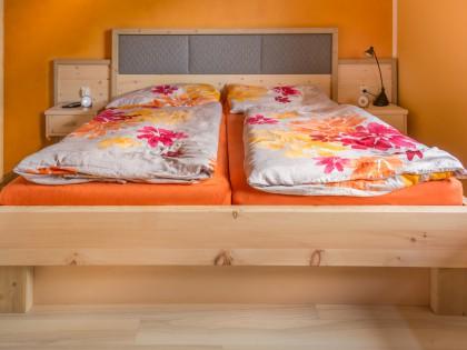Doppelbett mit Wandpaneele und Hängenachtkästchen